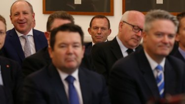 Dean Smith (front left) and Tony Abbott listen to Prime Minister Malcolm Turnbull during a Liberal party room meeting in November.