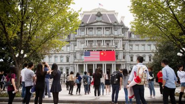 The Chinese flag is displayed next to the American flag on the side of the Old Executive Office Building in the White House complex in Washington, the day before a state visit by Chinese President Xi Jinping.