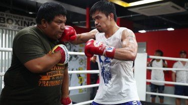 Manny Pacquiao hits the pads with Buboy Fernandez. By the end, the trainer is drenched in as much sweat as the fighter.