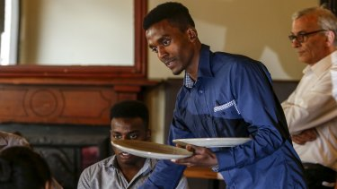 Melesse Asayhe (left) trains as a waiter with mentor Christos Vafeas (right) at the Empress Hotel.