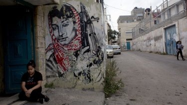 A Palestinian girl sits beside a mural of Palestinian militant Leila Khaled at the entrance of her family's home in the Aida refugee camp, ahead of the funeral procession of 13-year-old  Abdel Rahman Shadi.