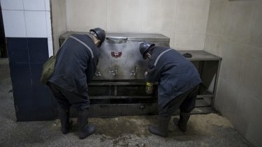 Workers fill up bottles with boiled water before entering the mine.