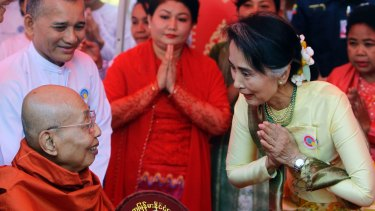 Myanmar State Counsellor and Foreign Minister Aung San Suu Kyi, right, pays respect to a monk during a ceremony at Upatasanti Pagoda earlier this month.