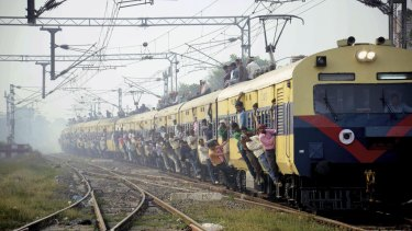 Indian passengers hang from the doors of the coaches of an overcrowded train in Bihar to travel home for the Chhath Puja festival earlier this month.