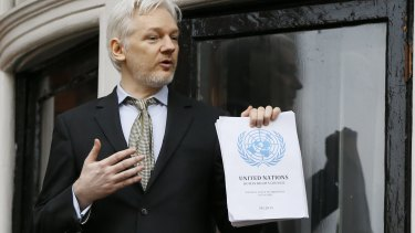 Julian Assange, pictured on the balcony of Ecuador's London embassy, with the UN report that says he is being 'arbitrarily detained' by Britain and Sweden.