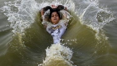 A girl cools off herself in the waters of the river Ganges in Allahabad, India.