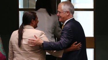 Mr Turnbull embraces Labor Senator Nova Peris after he delivered the report.