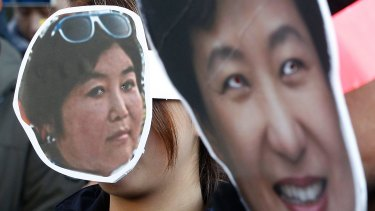 South Korean protesters wear masks of President Park Geun-hye, right, and Choi Soon-sil, while calling for Park to step down on Wednesday.