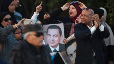 A small number of supporters of ousted former Egyptian President Hosni Mubarak hold posters with his photo, as they celebrate his acquittal, Cairo.