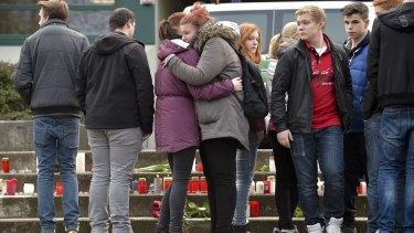 Students embrace in front of lit candles outside the Josef-Koenig-Gymnasium high school in Haltern am See.