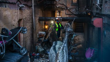 Police and workers inspect the building where 12 people died in a fire in the Bronx.