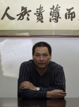 "Chinese lawyer Pu Zhiqiang, whose trial is throwing harsh light on the government's attitude to dissent. Above his head is a saying of Confucius: ""He who puts more blame on himself and less on others for any faults can keep hatred and grievances away."""
