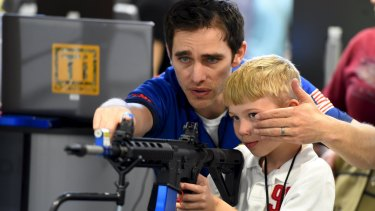 A boy is shown how to sight down an electronic rifle during the National Rifle Association's annual meeting in Nashville.