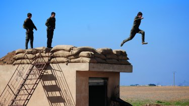 Three young YPG fighters prepare to leap from their lookout near the village of Tel Marouf, freed from the Islamic State two days before.