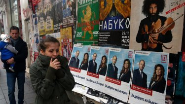 People walk in front of posters of Bulgarian Socialists Party candidate Rumen Radev in Sofia, Bulgaria.