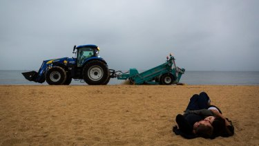 A partygoer sleeps on St Kilda beach as the post- New Year's Eve clean-up begins on Sunday.