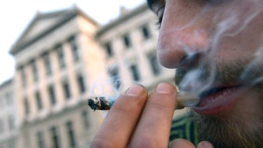 A man smokes marijuana outside Uruguayan Congress during a debate to legalize marijuana and regulate production and distribution.