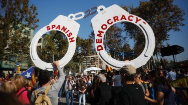 Protesters hold fake handcuffs as they take part a rally outside the Catalan parliament in Barcelona.