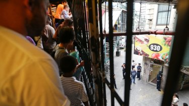 People watch as the police investigate a store in Brooklyn on the day after the mass overdose in July.