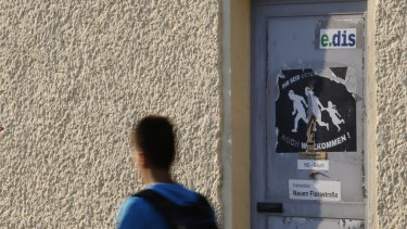 """A boy walks past a torn poster that reads """"You are neither refugees nor are you welcome"""" in Nauen, eastern Germany."""