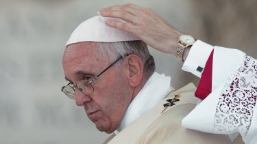 A master of ceremonies adjusts Pope Francis' skull-cap during a Mass in June