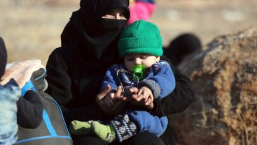 A Syrian woman holds a child at the refugee camp.