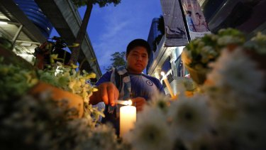 A man lights a candle near the Erawan Shrine at Ratchaprasong intersection the day after the explosion.