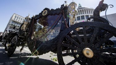 A horse-drawn carriage containing the coffin of purported Mafia boss Vittorio Casamonica is driven past the Don Bosco church during the funeral ceremony in Rome.