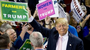 """Republican presidential candidate Donald Trump holds up a campaign sign that reads """"Farmers for Trump"""" after speaking at a rally at Valdosta State University in Valdosta, Georgia."""