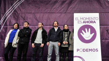 """Podemos leaders on stage at the rally. The placard reads: """"The moment is now - Podemos (We Can)""""."""