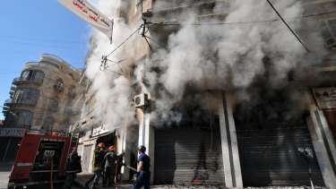 Lebanese firefighters tackle a blaze that broke out during clashes between the Lebanese army and Islamist gunmen.