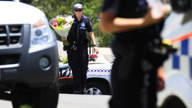 A police officer takes flowers delivered by a neighbour to the scene where Ms Bradford and her estranged husband's bodies were found.