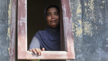 An ethnic Rohingya woman weeps as she looks out from a temporary shelter for migrants whose boats washed ashore in Lapang, Aceh province, Indonesia.
