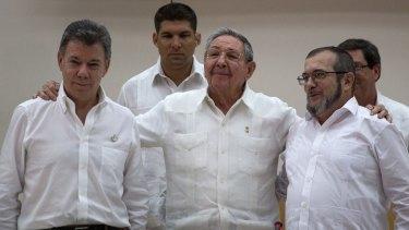 Cuban President Raul Castro, centre, embraces Colombian President Juan Manuel Santos, left, and FARC commander Timoleon Jimenez.