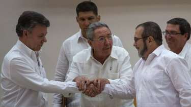 """Cuba's President Raul Castro, centre, encourages Colombian President Juan Manuel Santos, left, and the commander the Revolutionary Armed Forces of Colombia, or FARC, Timoleon Jimenez, known as  """"Timochenko"""", to shake hands in Havana on Wednesday."""