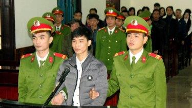 Blogger Nguyen Van Hoa, centre, stands on trial in Ha Tinhi, Vietnam, on Monday.