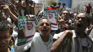 Demonstrators in support of the Saudi intervention hold posters of Saudi King Salman in the south-western city of Taiz on March 29.