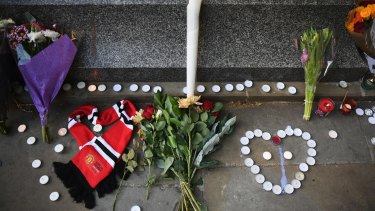 A Manchester United scarf, laid in the shape of a heart, lies next to flowers left by members of the public at a candlelit vigil to honour the victims of Monday evening's terror attack.