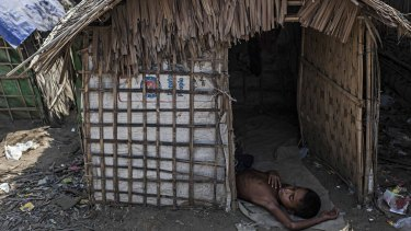 A Rohingya boy naps in his family's temporary shelter next to an internal displacement camp in Sittwe, Burma, in May.