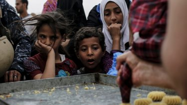 Children stare at a baker baking fresh cookies at a food distribution point in western Mosul, Iraq. Thousands of people still live in the western part of the city where food is getting scarce due to fighting between Iraqi forces and the Islamic State group.