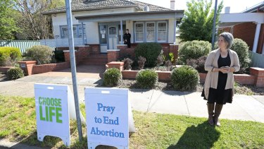 A protester stands outside the Fertility Control Clinic in Albury. A security guard mans the door to protect women entering.
