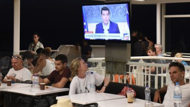 Greek Prime Minister Alexis Tsipras, announces his resignation on TV, watched by a tourist on a ferry in the Aegean sea.