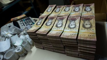 Stacks of banknotes are piled on a desk in a bakery in Caracas. Once one of the world's strongest currencies, the bolivar has been reduced to nuisance status.