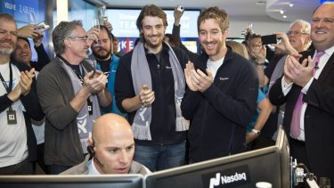 UNSW graduates and Atlassian co founders Mike Cannon-Brookes (left, with scarf) and Scott Farquhar watch as shares open on the Nasdaq.