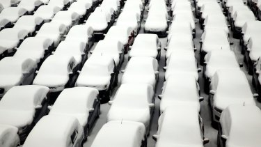 Snow covers vehicles in a rental car parking lot at O'Hare International Airport in Chicago.