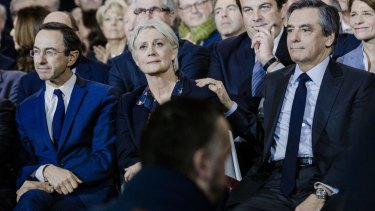 Francois Fillon, France's presidential candidate, right, puts a hand on the shoulder of his wife, Penelope Fillon, in Paris.