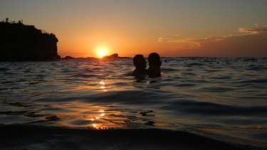 Sydney swelters through another night, as swimmers hit the beach just after 6am.