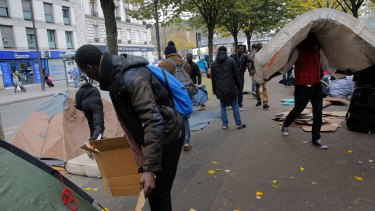 A migrants carries a mattress in a makeshift camp in Paris, on Friday.