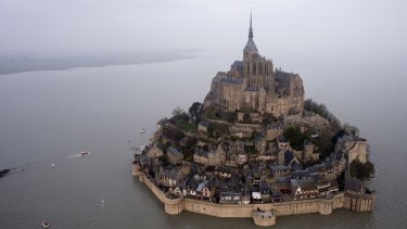 After: a supertide turns France's famed Mont Saint-Michel into an island.