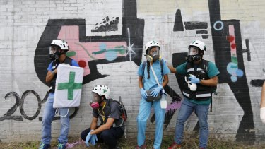 "Volunteer first responders from the ""Green Helmets"" stand on the sidelines of an anti-government protest in Venezuela."